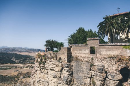 scenic view of stone wall, palms and building on rock against mountains landscape, Ronda, spain