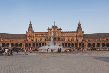 View of Spain Square with town hall and fountain under blue sky, Seville