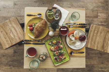 Photo for Top view of tasty healthy breakfast with cheesecakes and sandwiches on table - Royalty Free Image