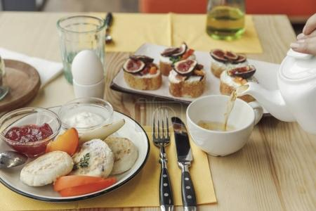 cropped shot of person pouring tea from teapot and tasty healthy breakfast on table