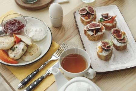 Photo for Close-up view of tasty healthy breakfast with cheesecakes fritters and canapes with figs on table - Royalty Free Image
