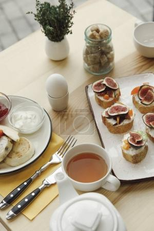 Photo for Close-up view of tasty healthy breakfast with tea and canapes with figs on table - Royalty Free Image