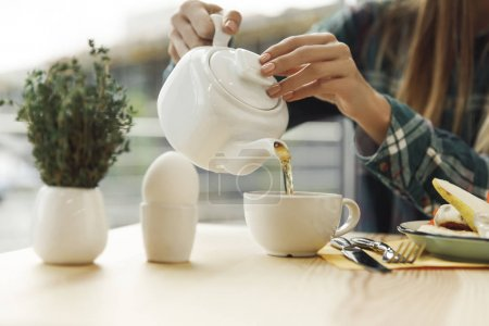 partial view of girl pouring tea from teapot in cup at breakfast