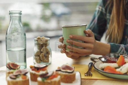 abgeschnittene Aufnahme eines Mädchens mit einer Tasse Tee beim Frühstück
