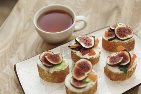 Photo for Close-up view of canapes with figs and cup of tea on table - Royalty Free Image