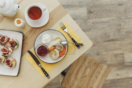 top view of tasty healthy breakfast with tea set on wooden table
