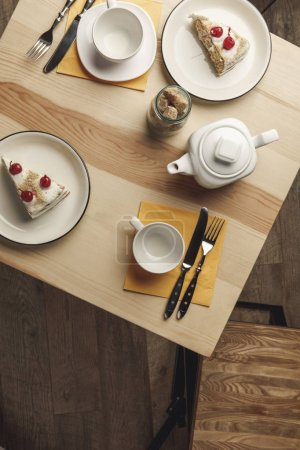 top view of teapot, empty cups and gourmet pastries on plates on wooden table