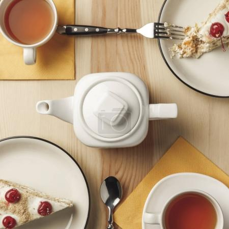 close-up top view of kettle, two cups with hot tea and delicious pastries on table
