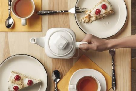top view of person holding teapot and tea set with pastries on table