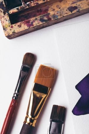top view of watercolor paints and paintbrushes with drawing album at designer workplace