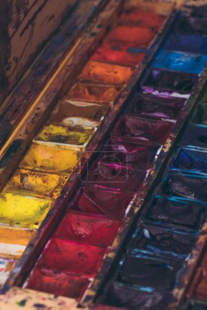 close-up view of watercolor paints in messy container