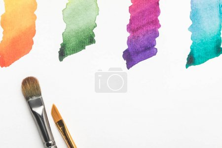 close-up view of paintbrushes and colorful bright paint strokes isolated on white
