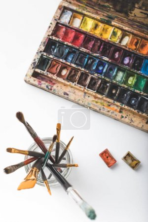 top view of watercolor paints and paintbrushes in glass on white