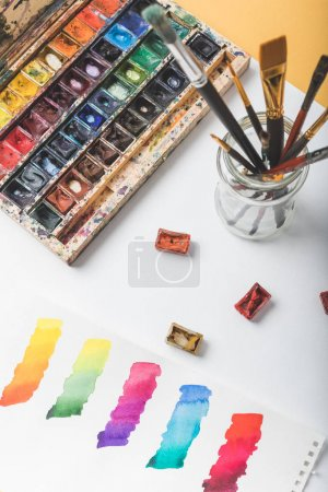 top view of watercolor paints, paintbrushes and colorful paint strokes in drawing album at designer workplace