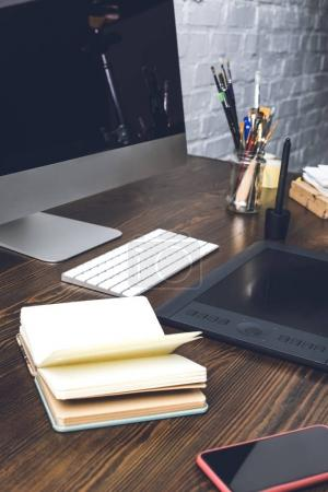 Photo for Close-up view of notebook, smartphone and graphics tablet at designer workplace - Royalty Free Image