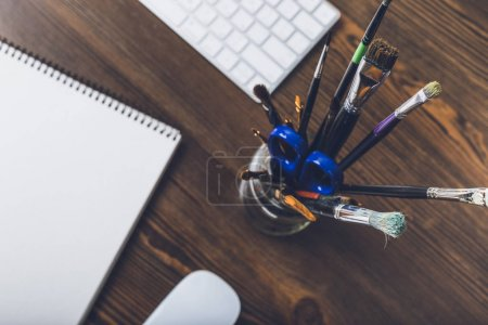 Photo for Top view of paint brushes with office supplies, drawing album, computer mouse and keyboard on table top - Royalty Free Image