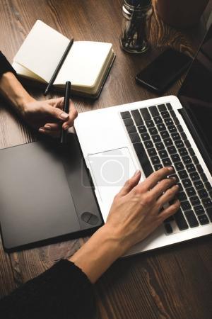 Photo pour Vue partielle rapprochée de la personne utilisant un ordinateur portable et une tablette graphique sur le lieu de travail - image libre de droit