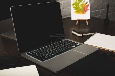 close-up view of designer workplace with notebooks and laptop with blank screen