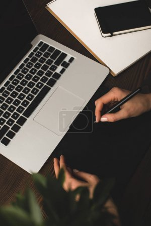 selective focus of person using laptop and graphics tablet at workplace
