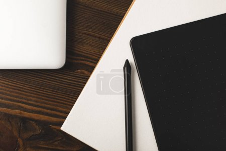 Photo for Top view of graphics tablet, laptop and drawing album on wooden table - Royalty Free Image