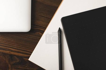 Photo pour Vue du dessus de la tablette graphique, ordinateur portable et album de dessin sur table en bois - image libre de droit