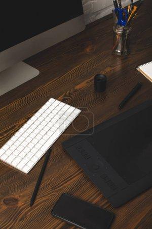 Foto de Vista cercana de la computadora, tableta gráfica y teclado sobre la mesa de madera - Imagen libre de derechos