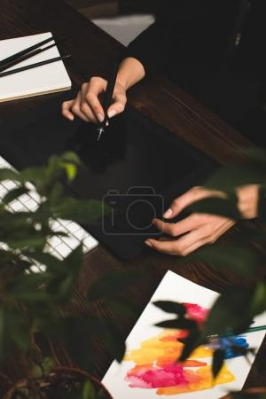selective focus of designer using graphics tablet at workplace