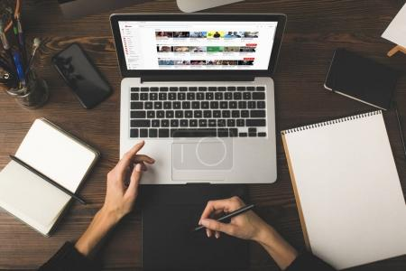 Photo for Cropped shot of designer using graphics tablet and laptop with youtube website on screen - Royalty Free Image