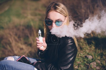 blonde girl vaping outdoors . female model smoking fruit flavored e-liquid or e-juice with vaporizer device or e-cig.Modern gadget for smokers