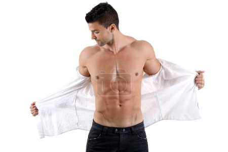 Handsome muscular male posing with unbuttoned shirt in front of white background