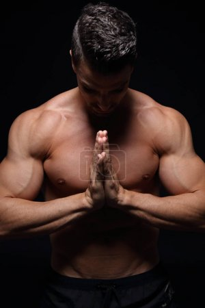 Handsome muscular male praying in front of black background