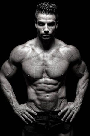 Bodybuilder exercising in front of black background