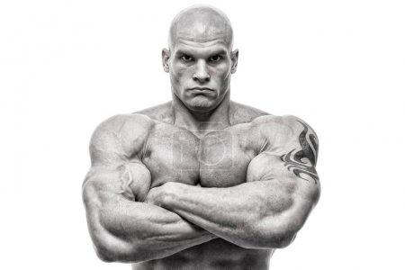 Bodybuilder exercising with kettlebells in front of white background