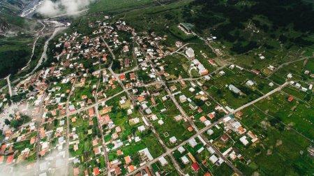 Photo pour Vue aérienne de la ville dans les montagnes verdoyantes avec nuages, Géorgie - image libre de droit