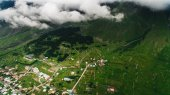 city in green mountains with clouds
