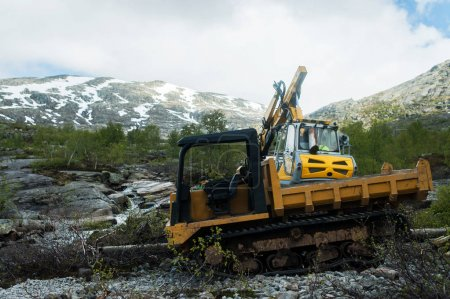 Photo for Yellow digger working on a road construction in mountain Norway - Royalty Free Image