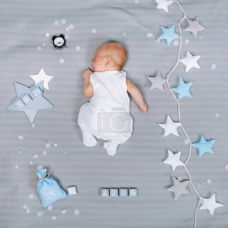 overhead view of adorable sleeping infant baby with decorations around
