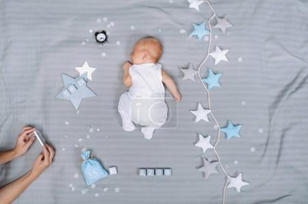 Foto de Recortado disparo de la madre tomando la foto del bebé dormido en el teléfono inteligente - Imagen libre de derechos