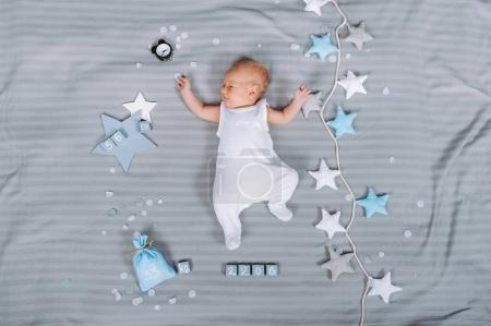 Foto de Vista aérea del adorable bebé recién nacido en traje de cuerpo acostado en la cama con decoraciones alrededor - Imagen libre de derechos