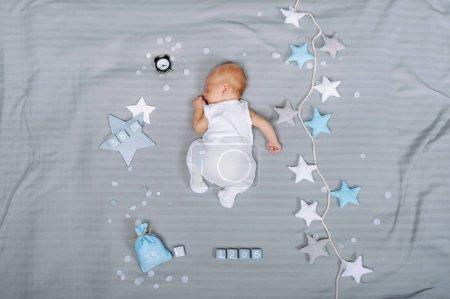 Foto de Vista aérea de adorable bebé dormido con decoraciones alrededor - Imagen libre de derechos