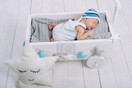 high angle view of cute newborn baby sleeping in wooden baby crib