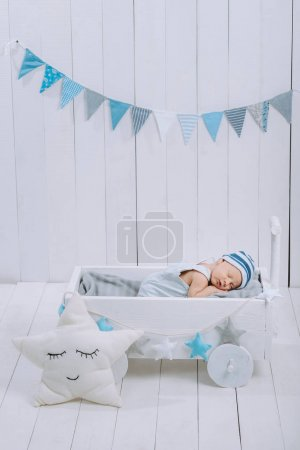 cute newborn baby in hat sleeping in wooden baby cot with star pillow near by