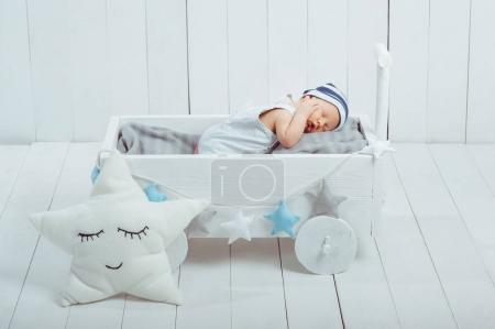 Photo for Portrait of adorable infant baby in hat sleeping in wooden baby cot decorated with stars - Royalty Free Image