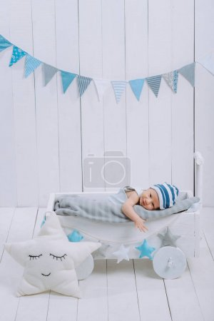 Photo for Innocent little infant baby lying in wooden baby cot - Royalty Free Image