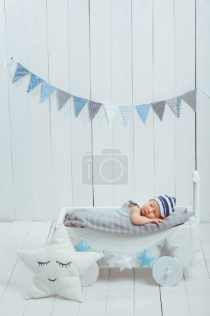 adorable infant baby in hat resting in wooden baby crib decorated with stars