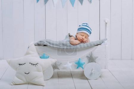 Photo pour Portrait d'adorable bébé en chapeau dormant dans un lit bébé en bois décoré d'étoiles - image libre de droit
