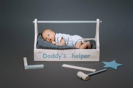 little baby in bodysuit lying in wooden toolkit with daddys helper lettering and hammer near by