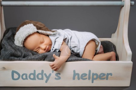 cute infant baby showing thumb up while sleeping in wooden toolbox with daddys helper lettering