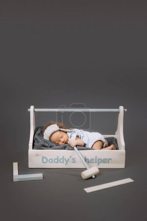 adorable baby with hammer in hand sleeping in wooden toolbox with daddys helper lettering