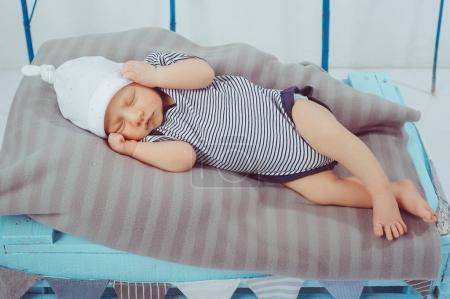 portrait of cute little sleeping baby in bodysuit and hat